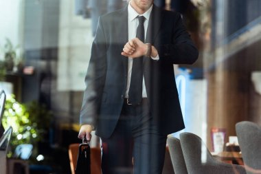 partial view of businessman with suitcase checking time while walking in cafe