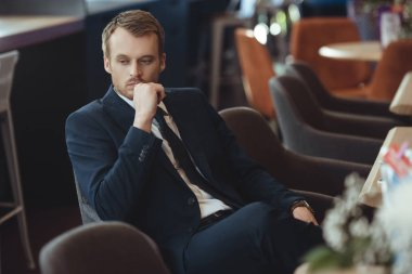 portrait of thoughtful businessman resting in coffee shop