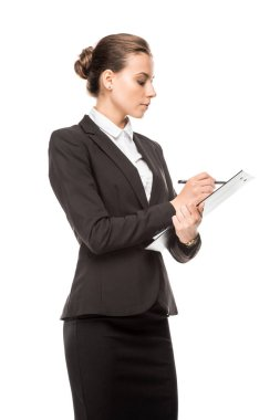 Side view of beautiful young businesswoman writing in clipboard isolated on white stock vector