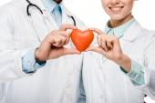 oříznutý obraz mladých lékařů v lékařských pláštích zobrazující symbol srdce izolované na bílém