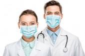 portrét radost mladých lékařů v lékařské masky při pohledu na fotoaparát izolované na bílém