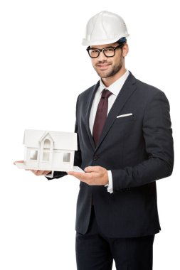 young male architect in hard hat showing miniature house isolated on white