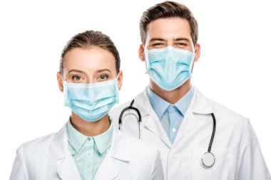 Portrait of happy young doctors in medical masks looking at camera isolated on white stock vector