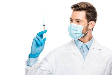 smiling young male doctor in latex gloves and medical mask holding syringe isolated on white