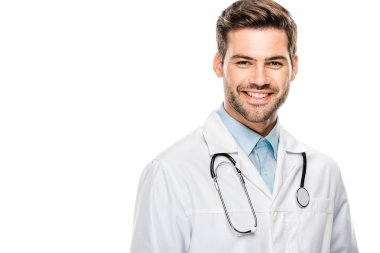 happy male doctor in medical coat with stethoscope over neck looking at camera isolated on white