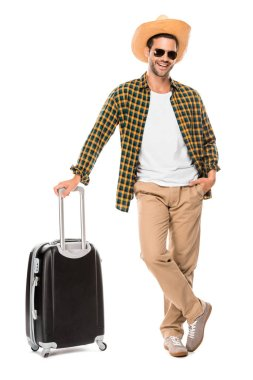happy young male traveler in sunglasses and straw hat standing with wheeled bag isolated on white