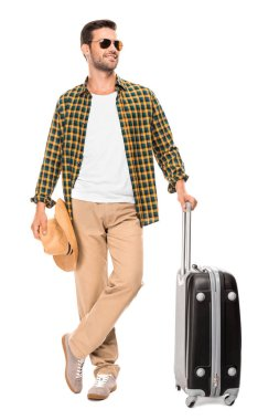 Smiling young male traveler in sunglasses standing with wheeled bag isolated on white stock vector