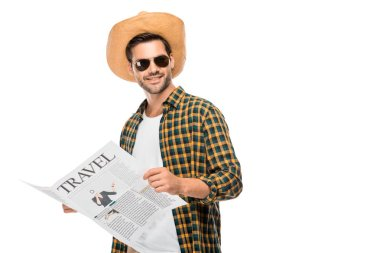 happy young male traveler in sunglasses reading travel newspaper isolated on white