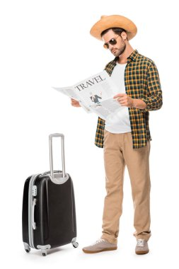 Stylish male tourist in sunglasses reading travel newspaper near wheeled bag isolated on white stock vector