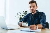 Fotografie Junger Geschäftsmann Notizen während der Teilnahme an Webinar auf Tischplatte mit Laptop im Büro