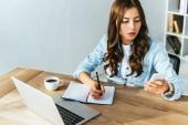 Fotografie junge Frau mit Smartphone auf Tischplatte mit Laptop Teilnahme Webinar im Büro