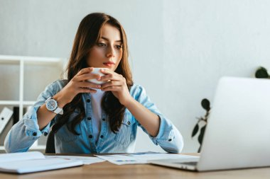 portrait of concentrated businesswoman with cup of coffee at workplace with papers and laptop in office