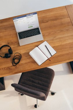 top view of laptop with facebook website, headphones and notebook on wooden table with office chair near by