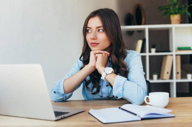 pensive woman at tabletop with laptop taking part in webinar in office