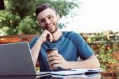 glücklicher schöner Mann nimmt an Webinar im Freien teil und schaut in die Kamera