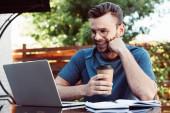 glücklicher schöner Mann, der an einem Webinar im Freien teilnimmt