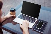 levágott kép az ember használ laptop-val üres képernyő, utcai kávézó asztal