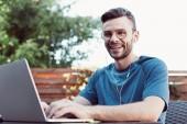 lächelnder schöner Mann, der an einem Webinar teilnimmt und in die Kamera schaut
