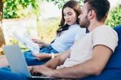 Kollegen nehmen an Webinar auf Sitzsäcken im Park teil und betrachten Dokumente