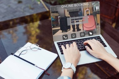 cropped image of girl using laptop with online booking appliance at table in street cafe