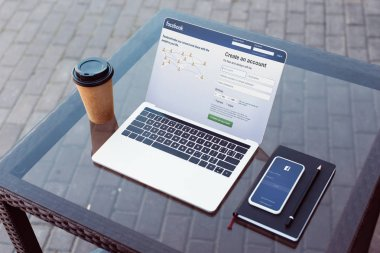 laptop and smartphone with loaded facebook pages on table on street