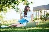 schönes Mädchen nimmt an Webinar teil und winkt während der Videokonferenz