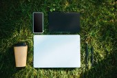 Fotografie elevated view of digital devices and disposable coffee cup on green grass in park