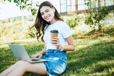 Smiling beautiful girl taking part in webinar with laptop in park, looking at camera stock vector