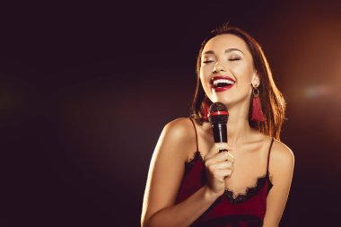 portrait of seductive woman with microphone in hand singing karaoke