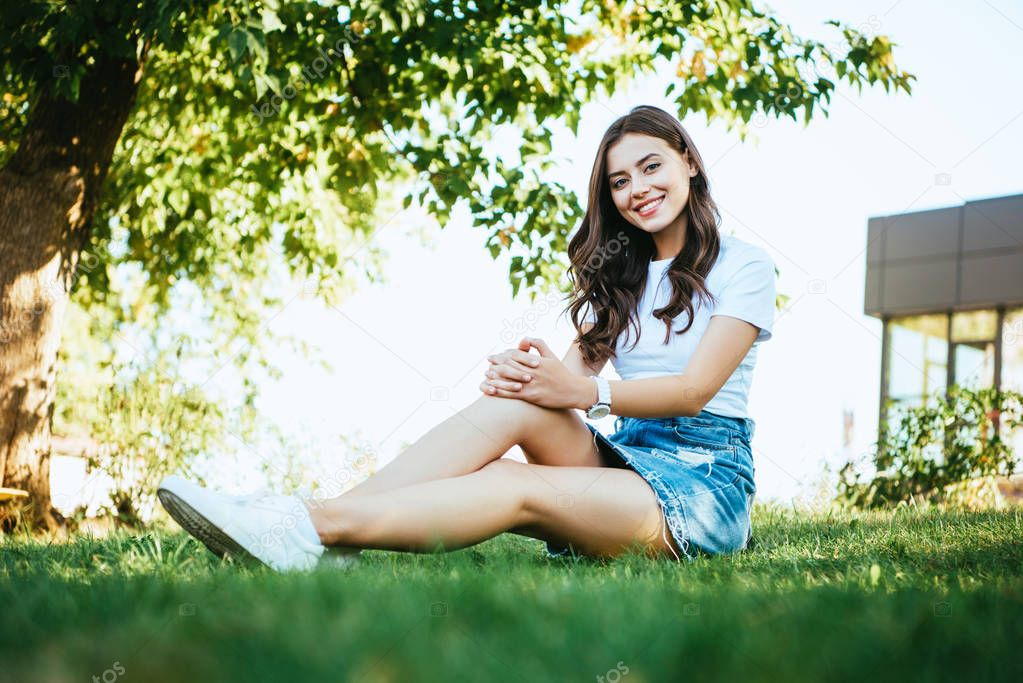 smiling beautiful girl sitting on green grass in park and looking at camera