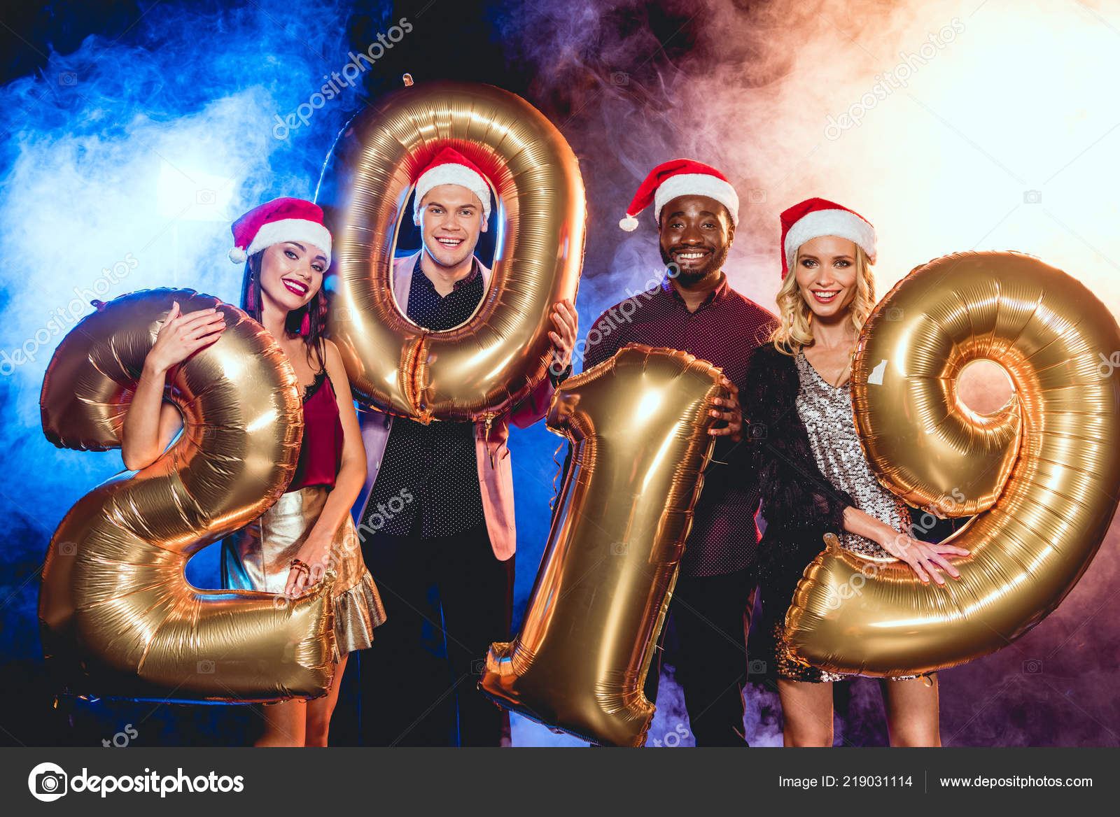 c065ea5dd1517 Glamorous friends in santa hats holding 2019 new year golden balloons on  black with smoke and backlit — Photo by ...