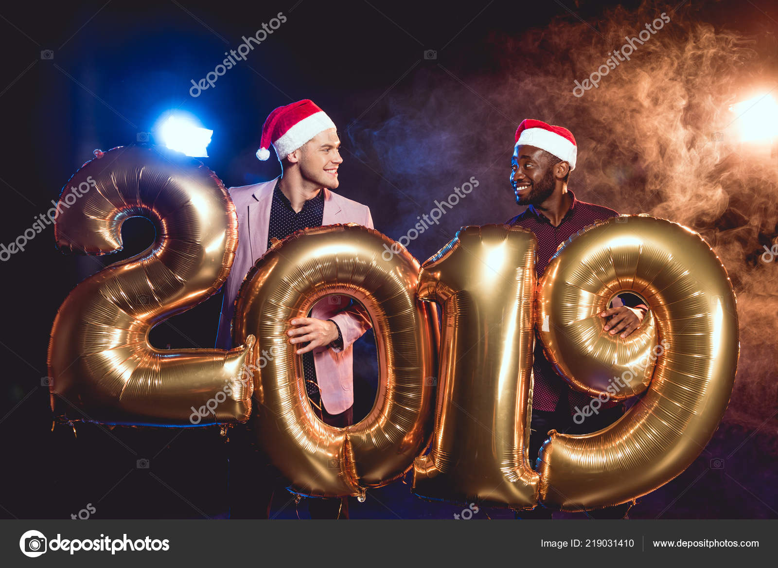 a018611bc0de4 Multicultural friends in santa hats looking at each other while holding  2019 new year golden balloons on smoke and backlit — Photo by ...