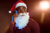 Fotografie african american man adjusting santa beard on black with backlit
