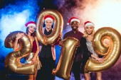 glamorous friends in santa hats holding 2019 new year golden balloons on black with smoke and backlit