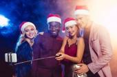 Fotografie happy multiethnic friends in santa hats taking selfie on smartphone