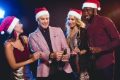Fotografie multicultural glamorous boyfriends and girlfriends in santa hats with champagne on new year party