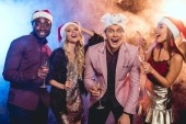 Fotografie excited multiethnic friends in santa hats celebrating new year with champagne glasses on party