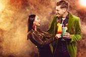 Fotografia eccitato la coppia glamour che clinking con bicchieri da cocktail sul partito con fumo
