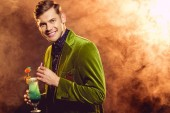 handsome smiling man in green jacket holding alcohol cocktail on party with smoke