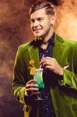 smiling man in green jacket holding sweet cocktail on new year party with smoke