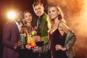 Fotografie glücklich multiethnischen Freunde Klirren mit Alkohol Cocktails auf party