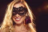 Krásná blondýna usměvavá dívka v černé karnevalové masky