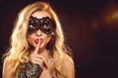 atraktivní blondýnka v karnevalové masce gestem mlčení