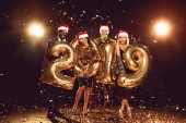 beautiful friends in santa hats holding 2019 new year golden balloons and standing on confetti with backlit
