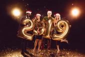 Fotografie Happy přátelé v santa klobouky drží nový rok 2019 zlaté balónky na konfety
