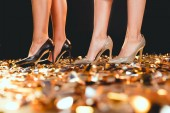 cropped view of girls in high heels standing on golden confetti on party