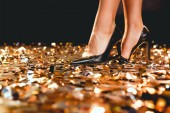 Photo cropped view of girl in black high heel shoes standing on golden confetti