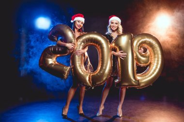 two happy women in christmas hats holding sign 2019 made by golden balloons on new year party with smoke