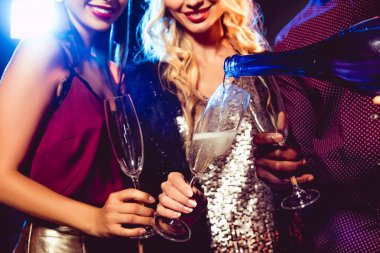 cropped view of man pouring champagne from bottle into glasses for glamor girls