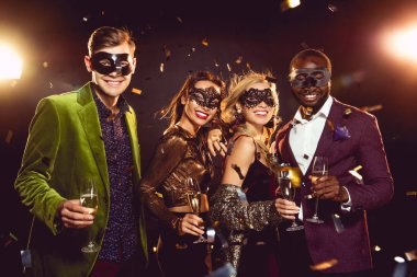 glamorous multiethnic friends in carnival masks holding champagne glasses and celebrating new year on party